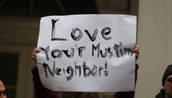 Hand-lettered Love Your Muslim Neighbor sign held aloft.