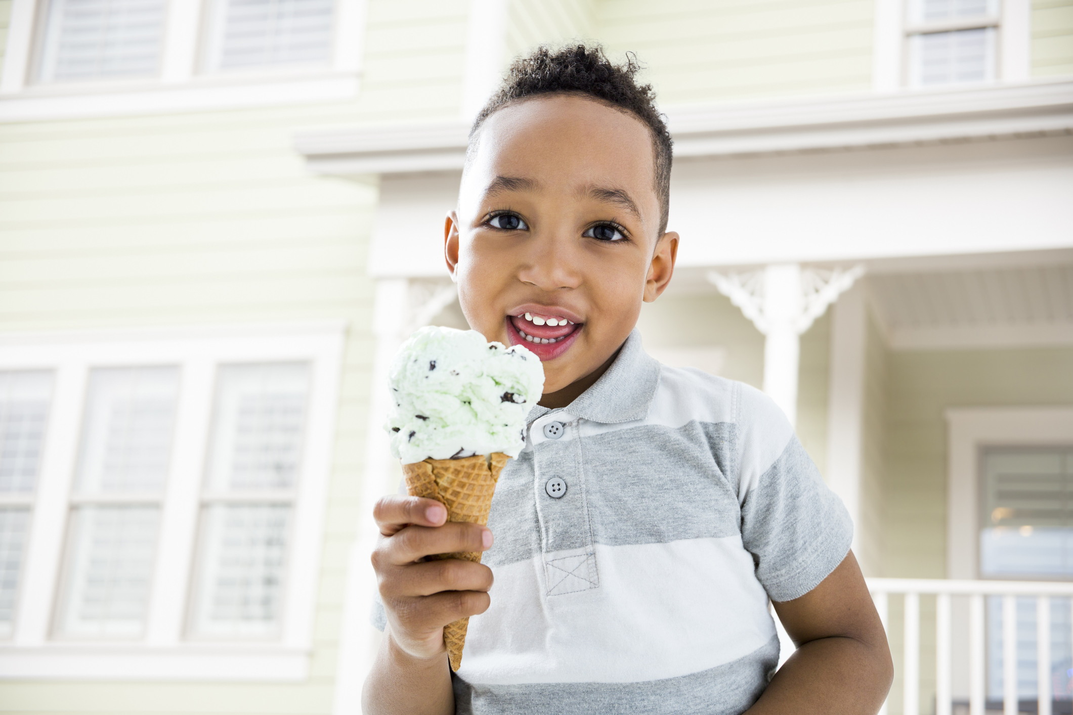Mixed race boy eating ice cream cone in backyard