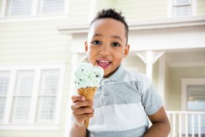 Mixed race boy eating ice cream cone in backyard