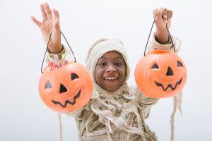 Black boy in mummy costume holding jack o'lanterns