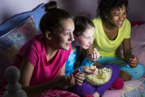 Preteen girls at sleepover watching tv, eating popcorn