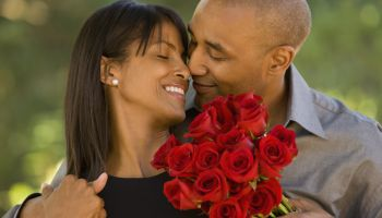 African American man giving flowers to wife
