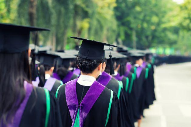Back of graduates during commencement at university. Close up at graduate cap. Color tone image.