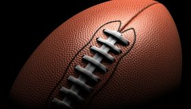 American football on black background, close-up