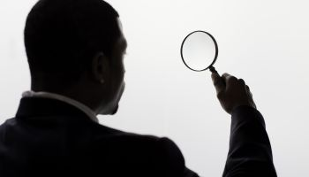 A man looking through a magnifiing glass.